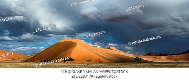 Panoramic landscape photo of a rainstorm over the dunes of Sossusvlei. Sossusvlei, Namib Naukluft National Park, Namibia