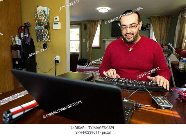 Man with visual impairment at his keyboard using a screen reader