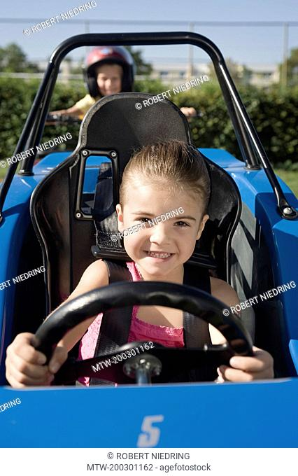 Smiling girl in vehicle on driver training area