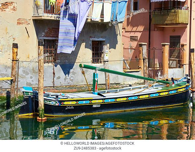 Colourful barge moored beneath canalside apartments with washing hanging out, Chioggia, Venetian Lagoon, Veneto, Italy, Europe