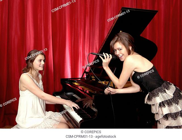 Two young woman improvising on stage with vocals and a grand piano