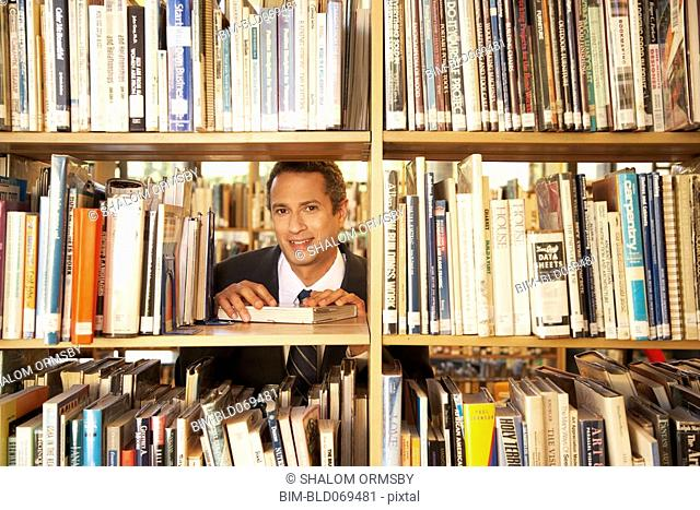 Hispanic man in suit looking through bookshelf in library