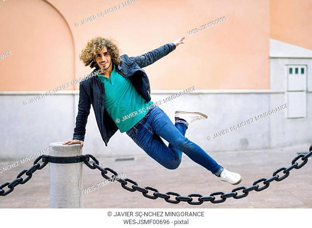 Portrait of smiling young man jumping over chain outdoors