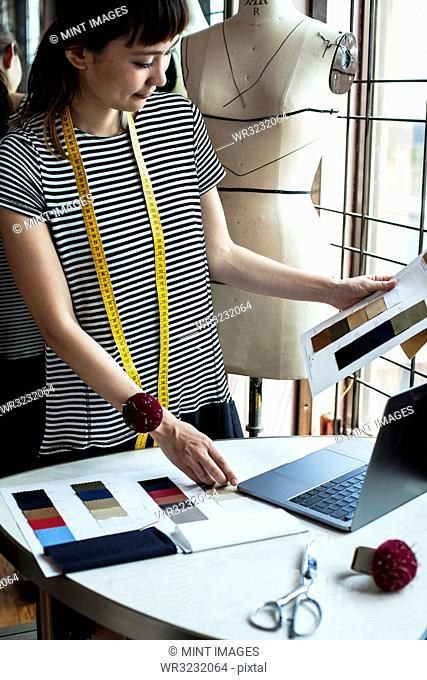 Japanese female fashion designer working in her studio, looking at fabric samples, using laptop