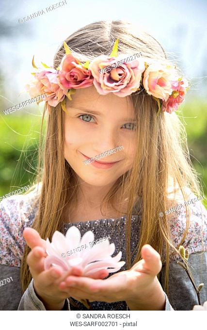 Portrait of smiling girl with wreath of flowers holding magnolia blossom in her hands