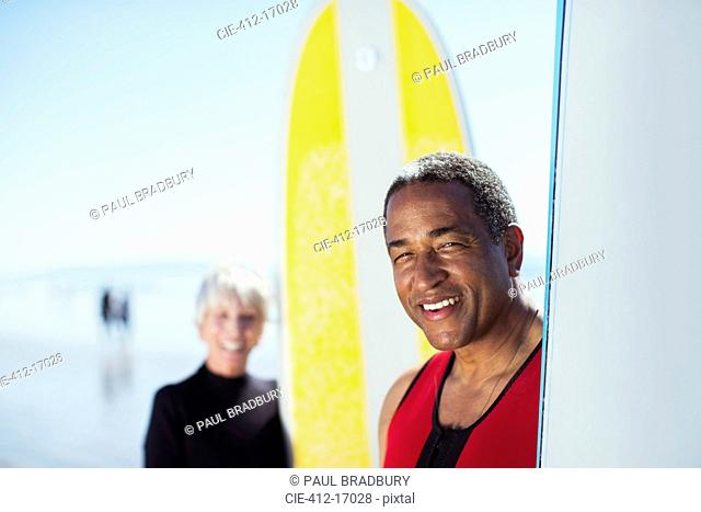 Portrait of senior couple with surfboards on beach