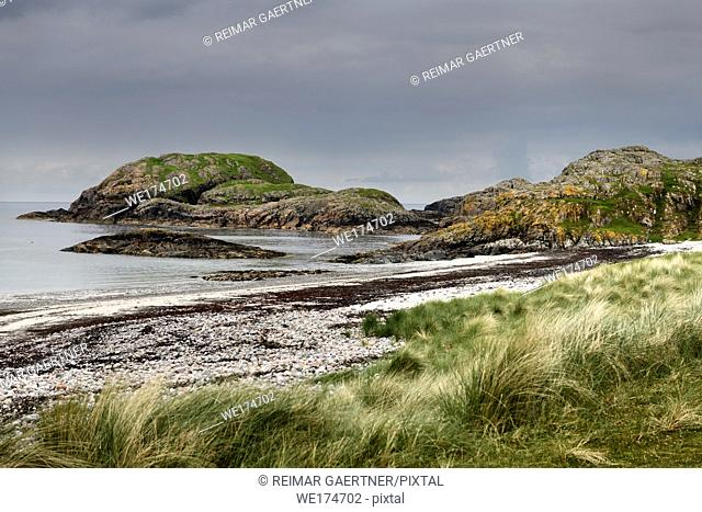 Seaside grass and granite outcropping on the shore of The Bay at the Back of the Ocean at The Machair on Isle of Iona Inner Hebrides Scotland UK