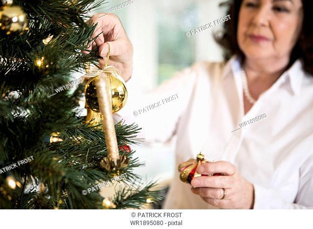 Senior woman decorating Christmas tree