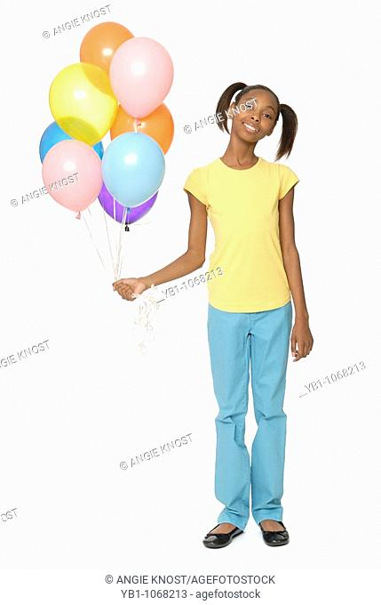 Ten year old girl holding balloons
