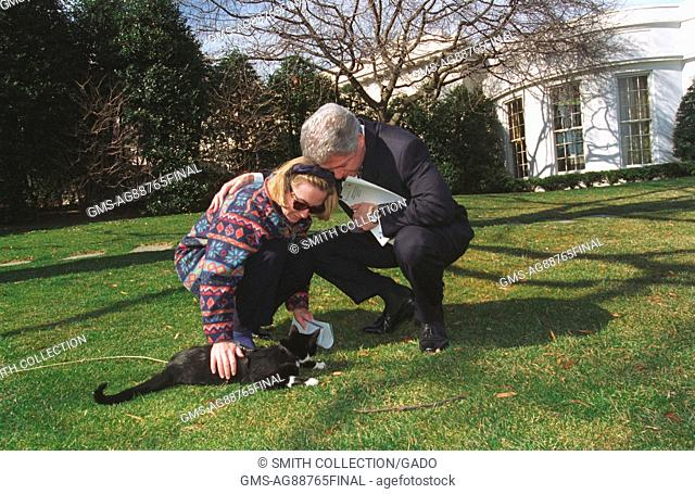 On the front lawn of the White House, President Bill Clinton wearing black suit and holding paper bends down beside First Lady Hillary Clinton wearing patterned...