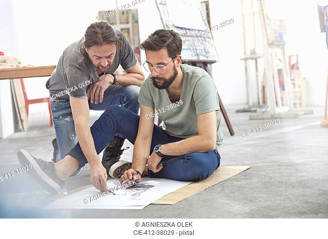Male artists sketching on floor in art class studio