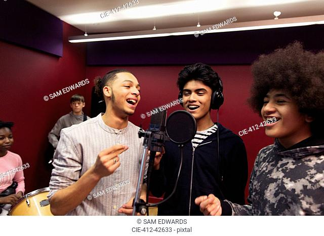 Smiling teenage boy musicians recording music, singing in sound booth