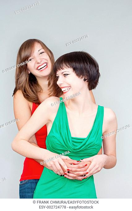 two happy young women standing, smiling - isolated on gray
