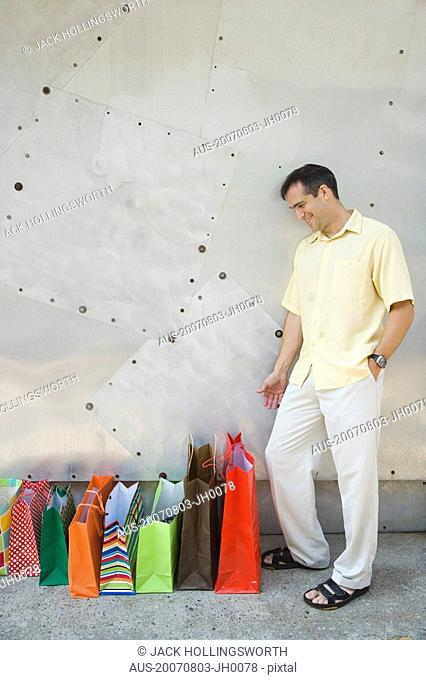Mid adult man looking at bags and smiling