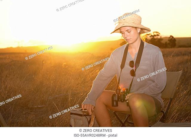 Young woman sitting on chair on safari, Stellenbosch, South Africa