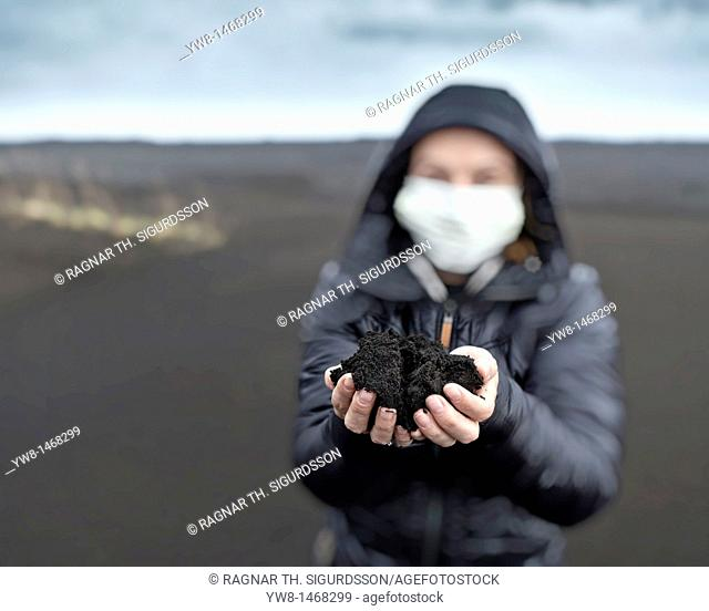 Woman holding new ash from recent Grimsvotn volcanic eruption, Iceland  Skeidararsandur outwash plains covered with ashfall  Eruption began on May 21, 2011