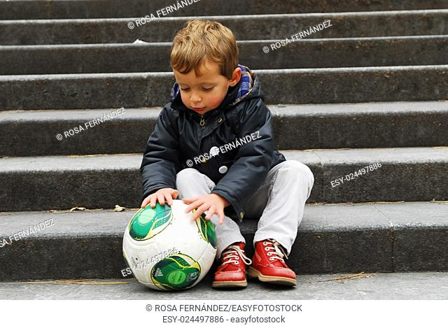 Baby boy playing with a football siting on a step, Madrid, Spain