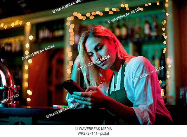 Waitress using her mobile phone