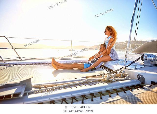 Serene, affectionate couple relaxing on sunny catamaran