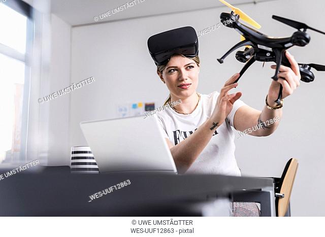 Young woman with laptop and VR glasses at desk holding drone