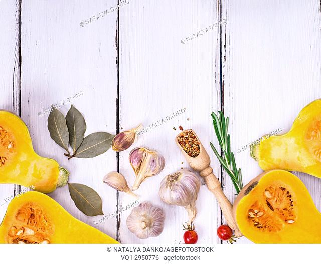fresh pumpkin on a white wooden background of parallel boards and garlic, top view, empty space at the top