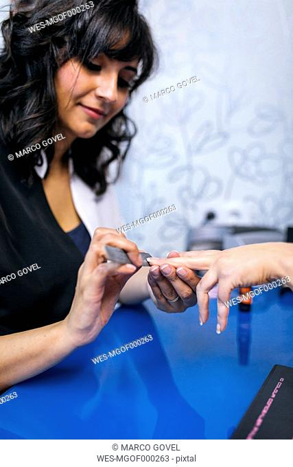 Cosmetician manicuring hands of female client