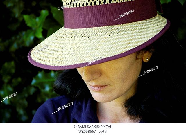 Portrait of a woman wearing a straw hat and looking sad