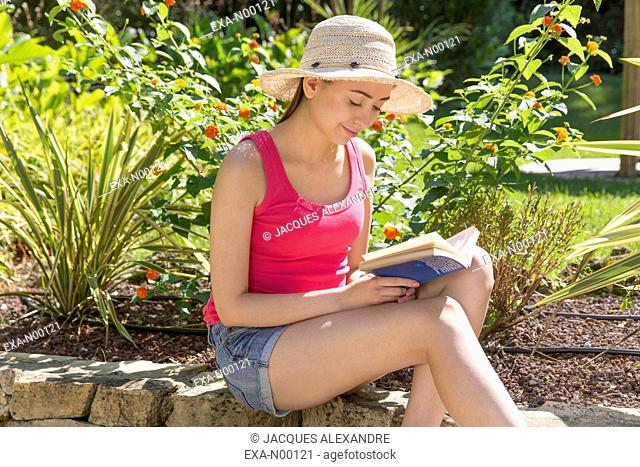 Young woman sitting in garden reads a book
