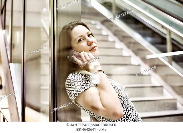 Young woman posing with smartphone behind a glass wall in an underground station, portrait, Cologne, North Rhine-Westphalia, Germany