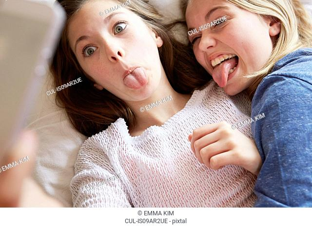 Two girls lying on bed sticking out tongues for smartphone selfie