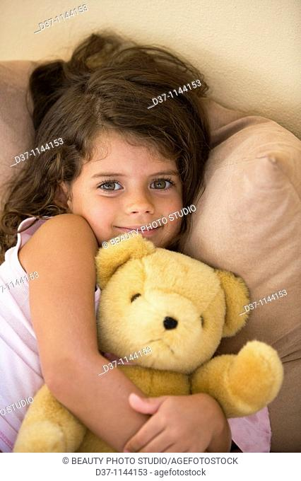 Caucasian girl hugging her teddy bear