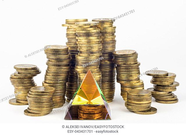 Glass pyramid in the foreground, in the background large stacks of coins