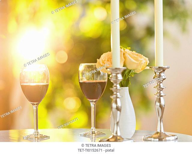 Still life with wine in glasses, candles and bouquet on table