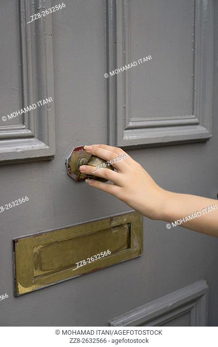 Woman's hand holding a door handle