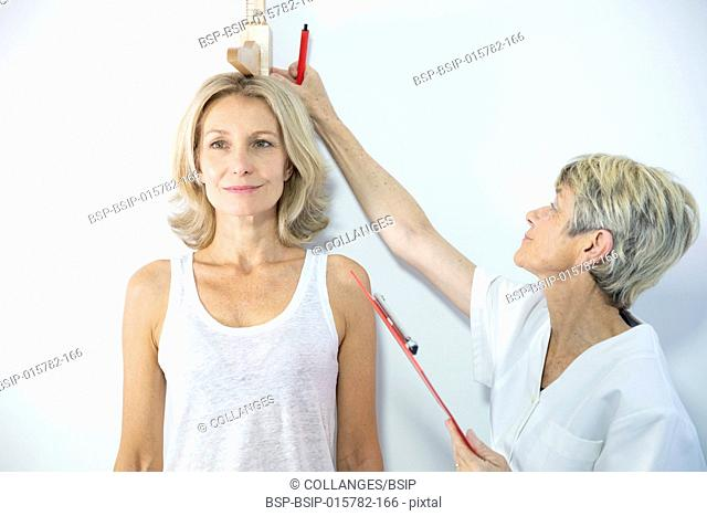 Woman measuring herself with a height measuring rod