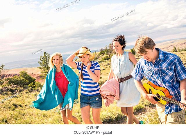 Young man and female friends playing ukulele and walking in hills, Bridger, Montana, USA