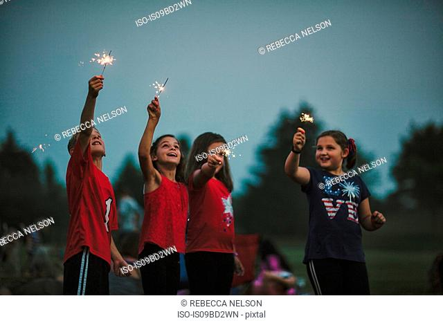 Group of friends, arms raised holding sparklers