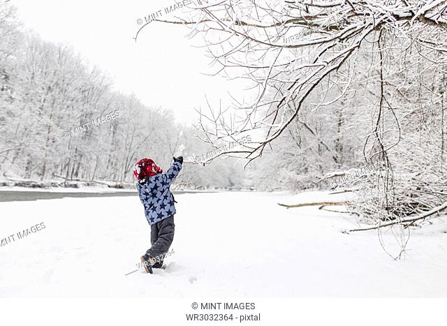 Boy wearing furry hat standing near a tree lined river in the snow, arm raised