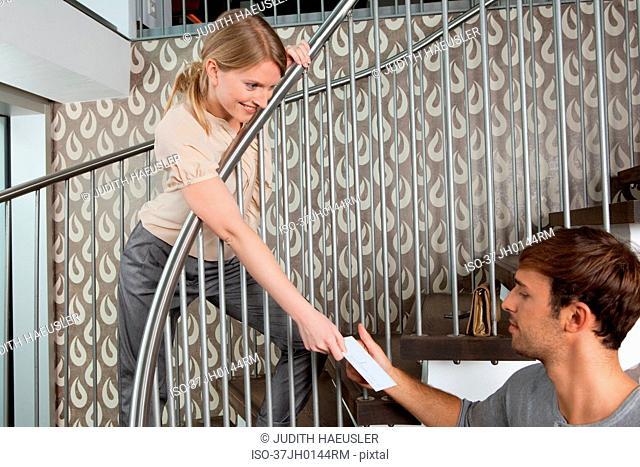 Woman handing postcard to boyfriend