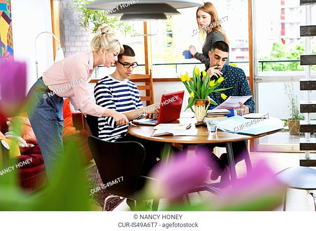 Four young adults sitting around table studying