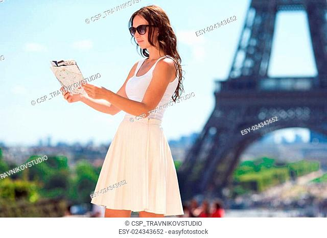 Happy young woman with a city map in Paris background the Eiffel tower