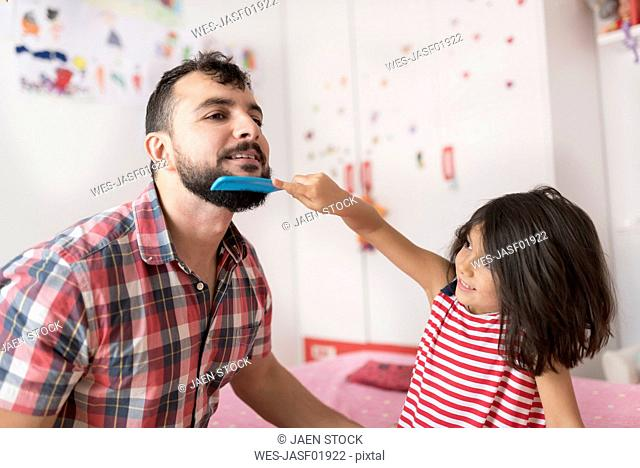 Little girl combing her father's beard