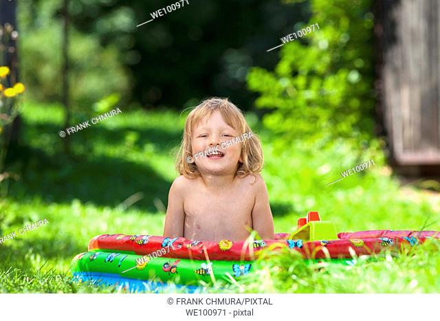 boy in inflatable pool in garden