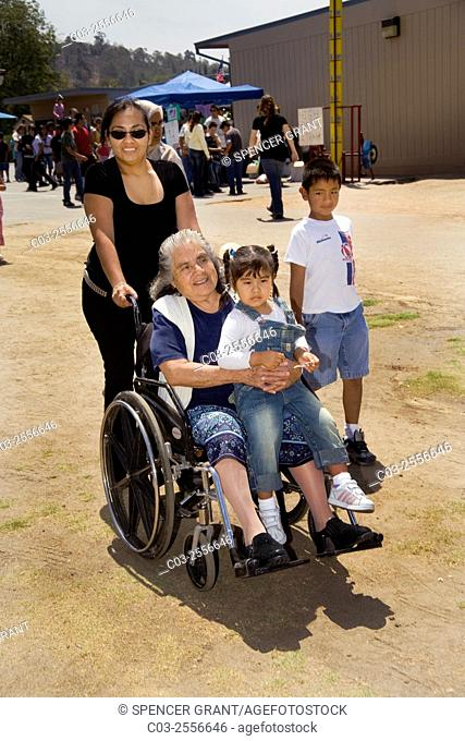 Three generations of a Hispanic family attend a community fair in Mission Viejo, CA, with grandmother in a wheelchair pushed by her daughter