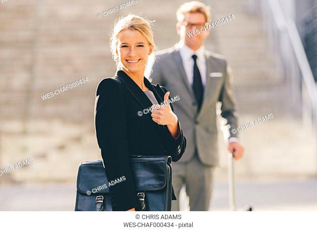 Optimistic businesswoman with businessman in background
