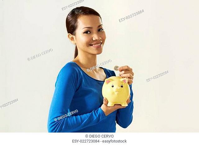 asian girl showing piggybank and euro coin