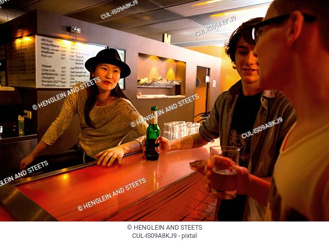Three people sitting at bar with alcoholic drinks