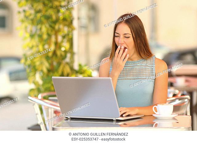 Tired woman yawning and working with a laptop in a restaurant during breakfast