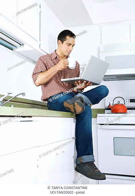 Hispanic man with laptop and coffee cup on kitchen counter
