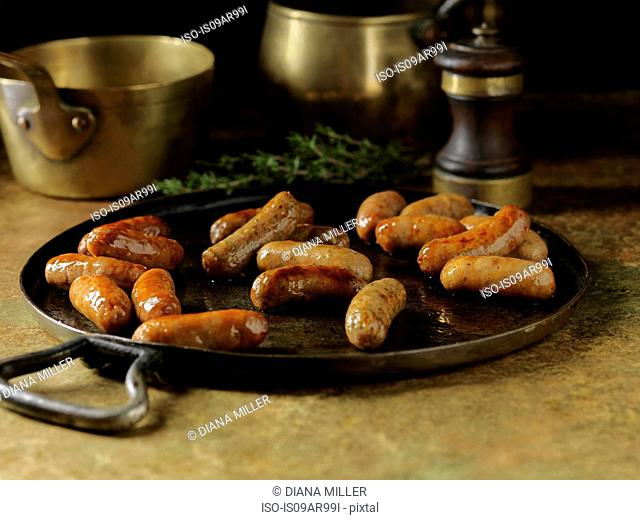 Rustic still life with fried cocktail sausages in metal serving dish